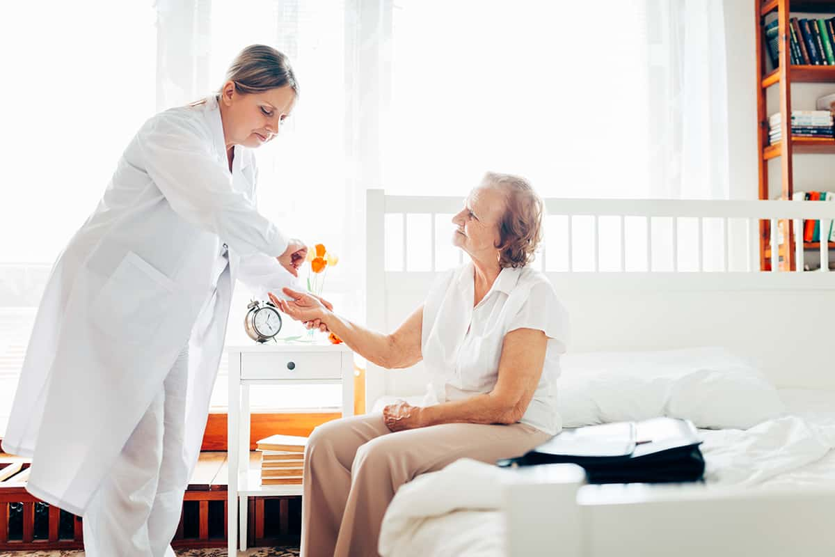 Providing care and support for elderly. Doctor visiting elderly patient at home.