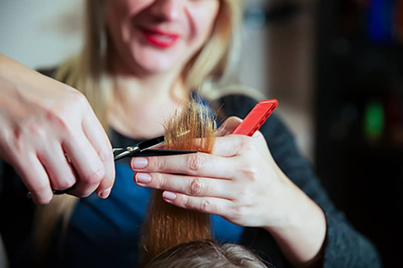 Young woman with long hair at hairdresser.Stylist making hairstyle with scissors and comb.