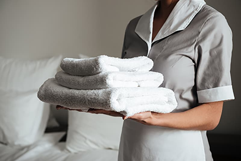 Cropped image of a young hotel maid standing and holding fresh clean towels